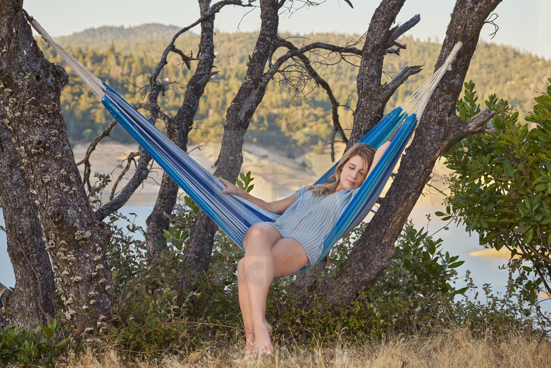 """""""Young Woman Relaxing in a Hammock Outdoors"""" stock image"""