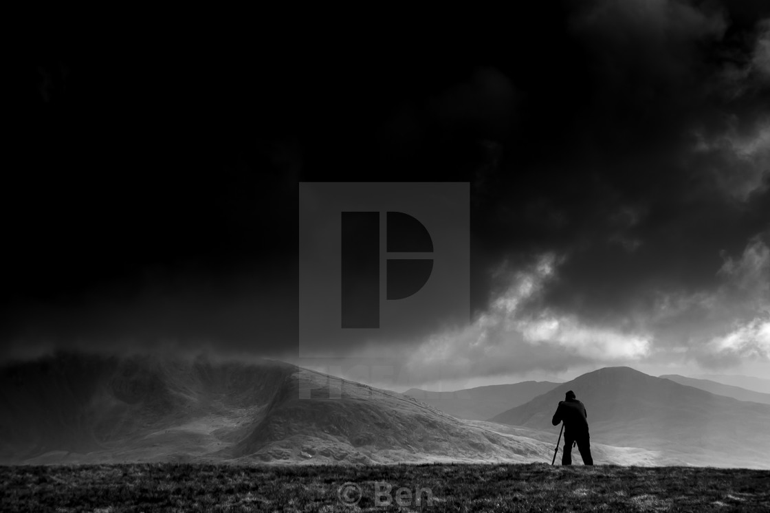 """A photographer at work high in the mountains"" stock image"