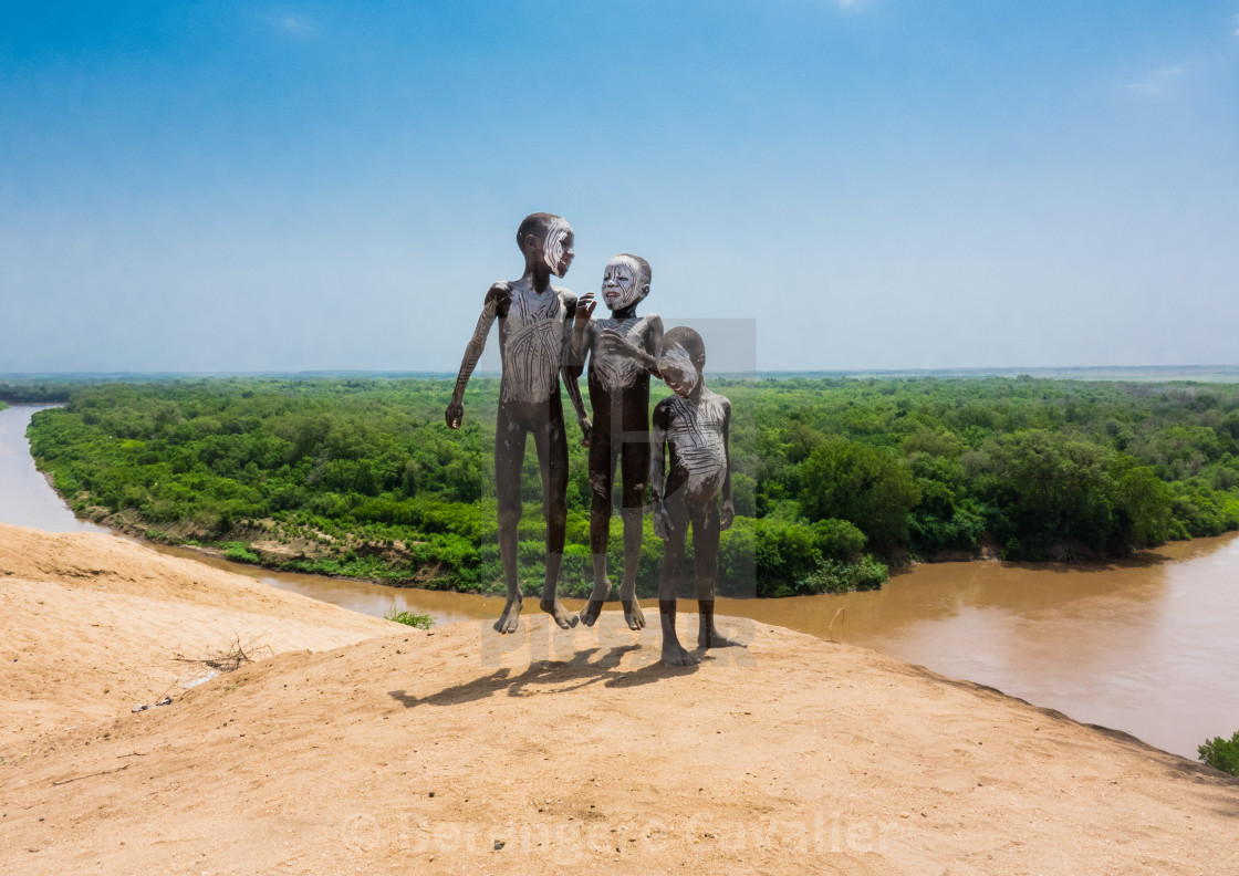 """Karo tribe kids jumping in front of Omo river, Omo valley, Korcho, Ethiopia"" stock image"