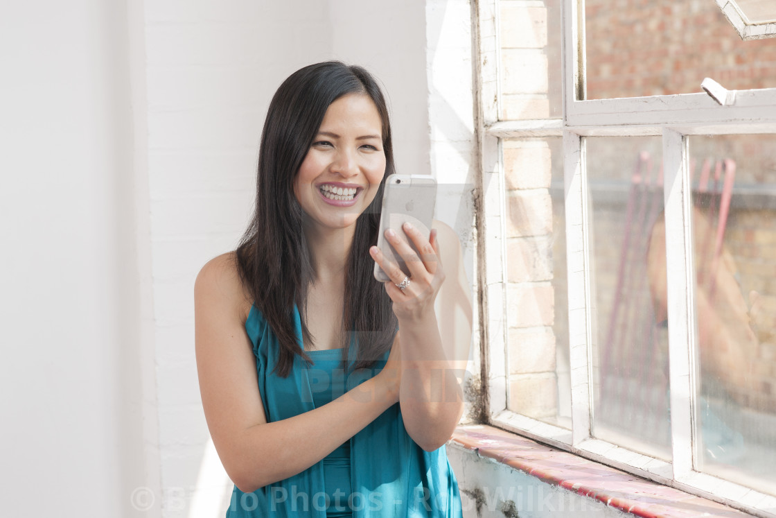 """asian woman using mobile phone for facetime, skype"" stock image"
