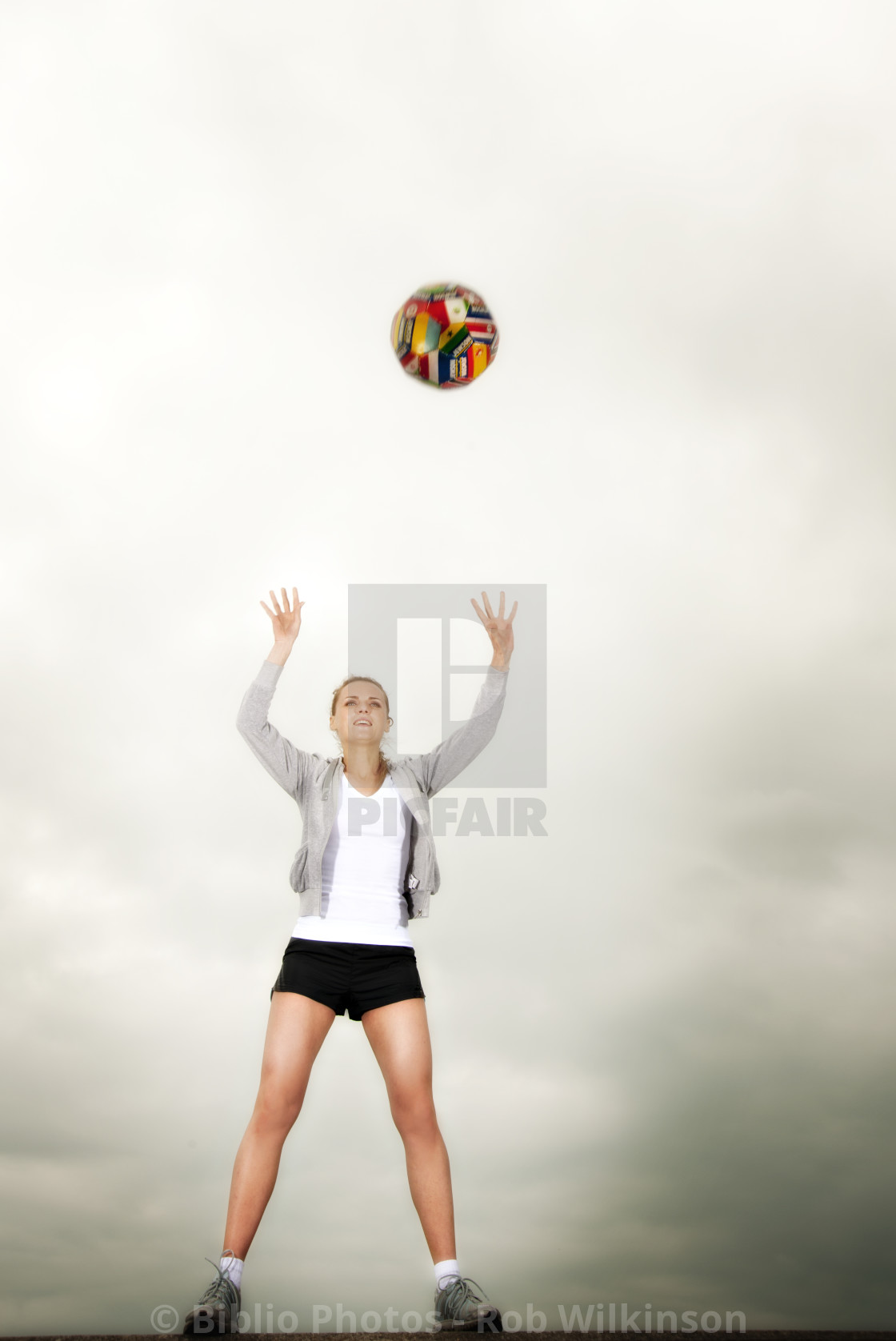 """woman throwing a football above her head"" stock image"