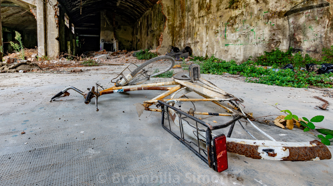 Bicycle fallen to the ground in an abandoned and ruined place