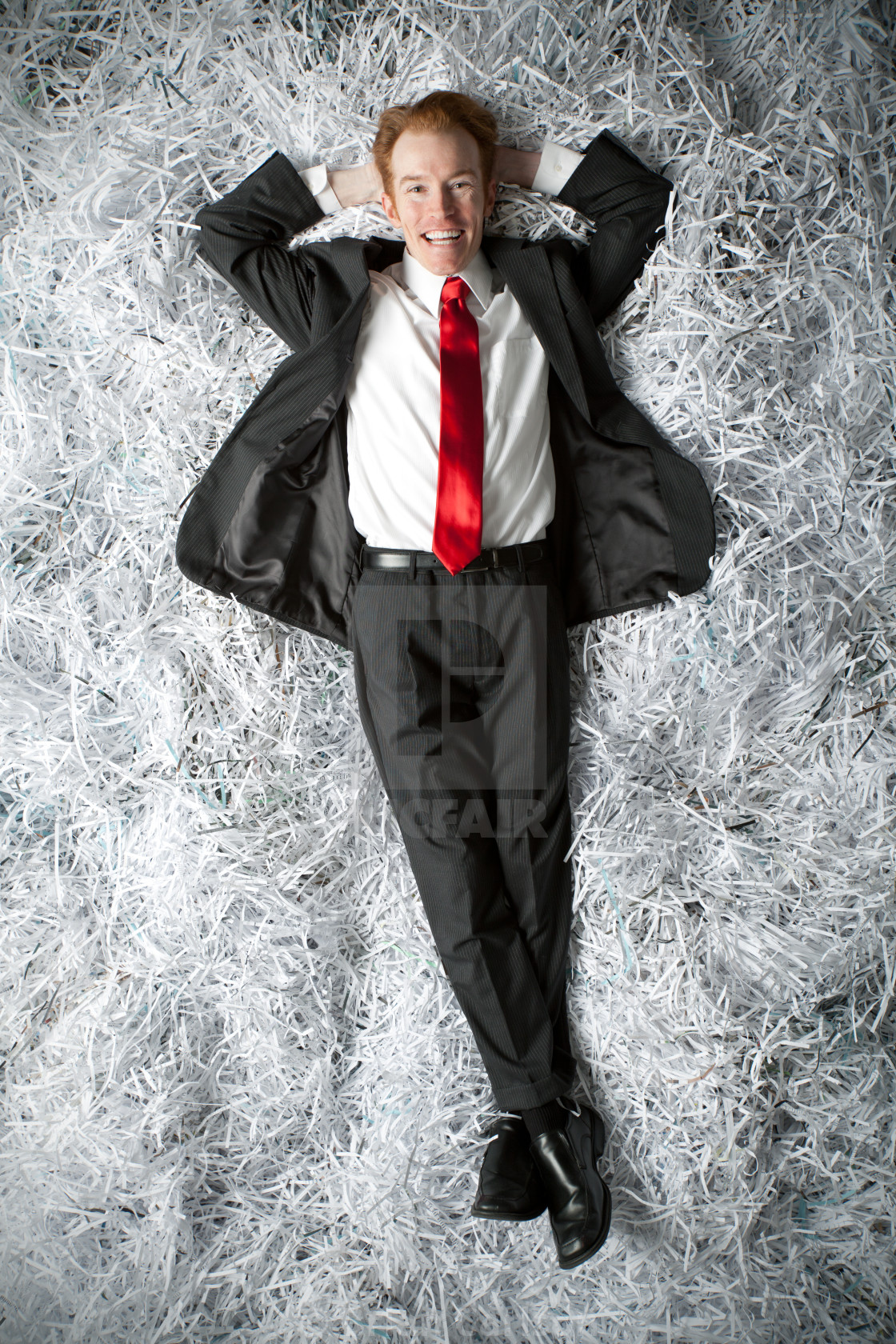 """""""Executive type lying on bed of shredded paper"""" stock image"""