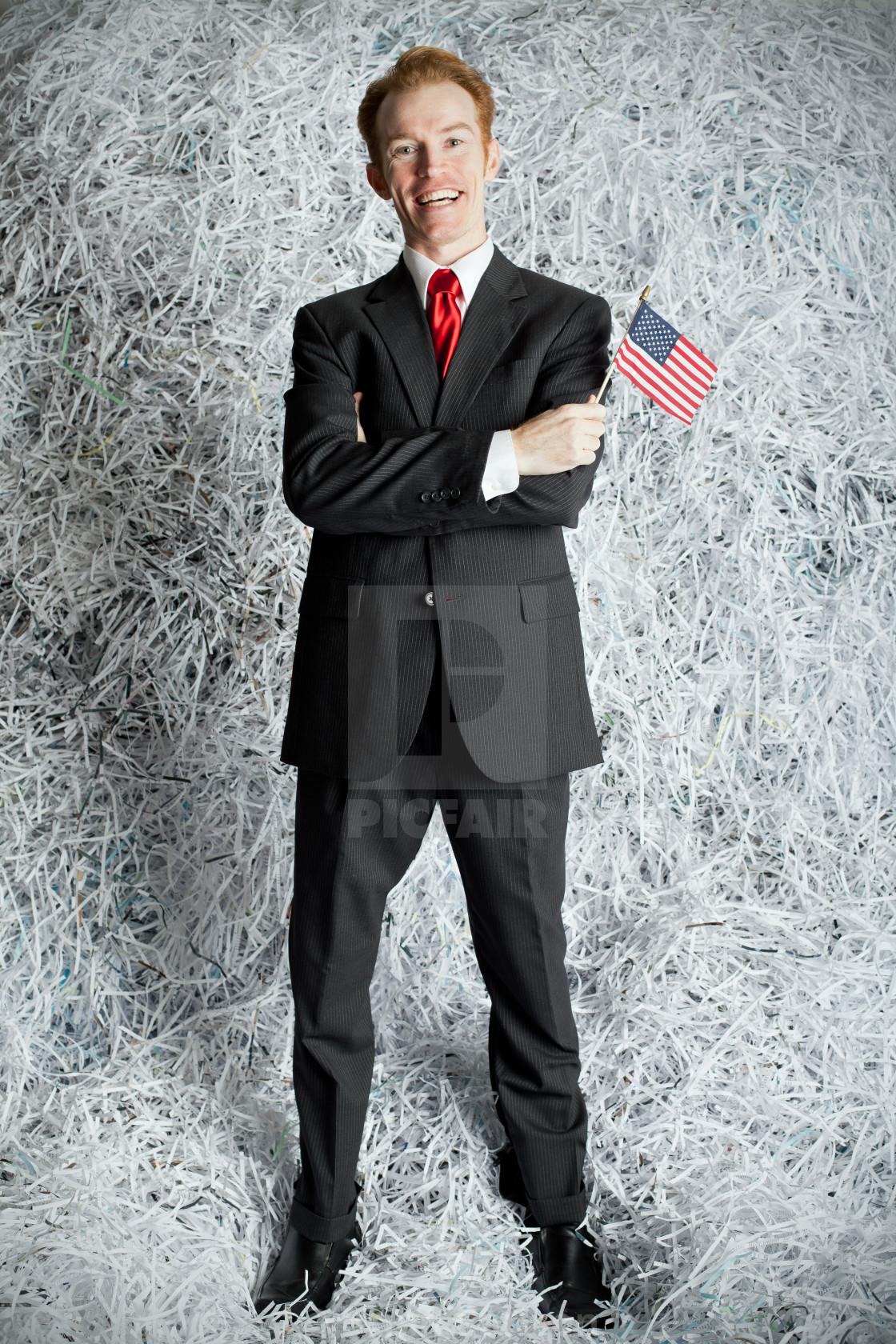 """Man holding miniature american flag standing against wall of shr"" stock image"