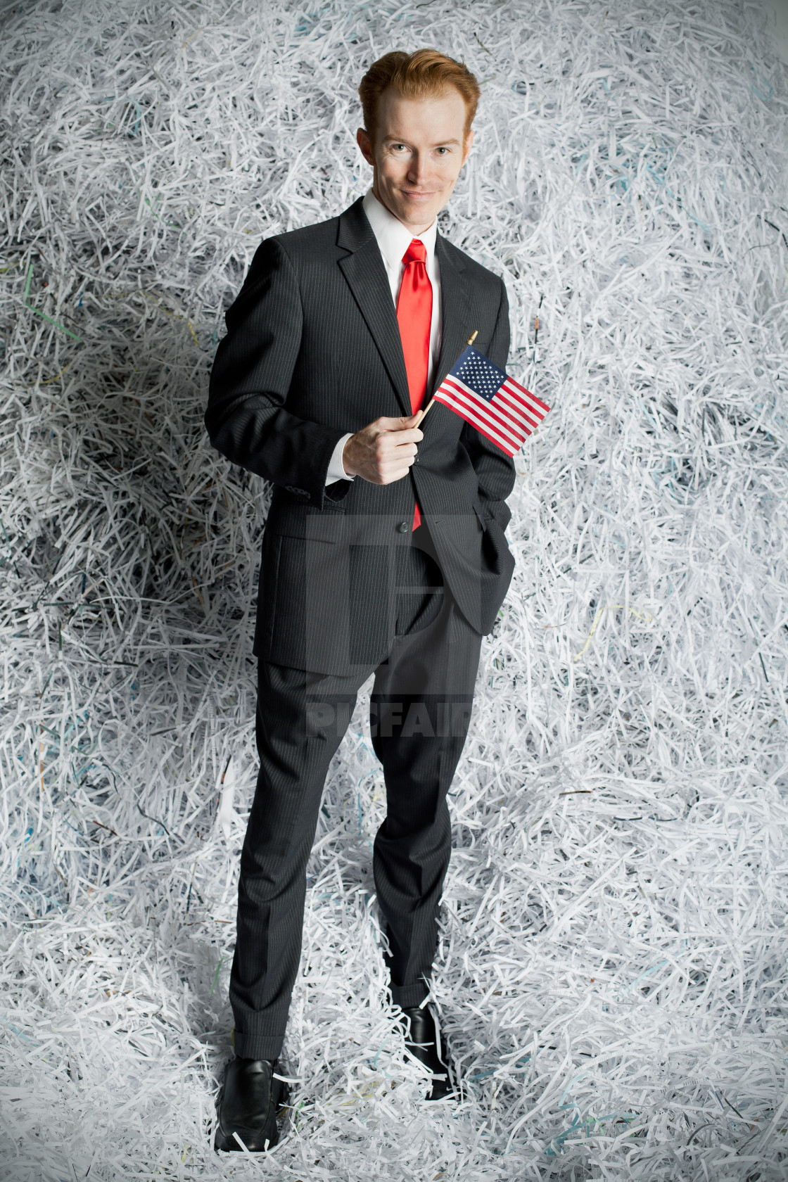 """""""Man holding miniature american flag standing against wall of shr"""" stock image"""