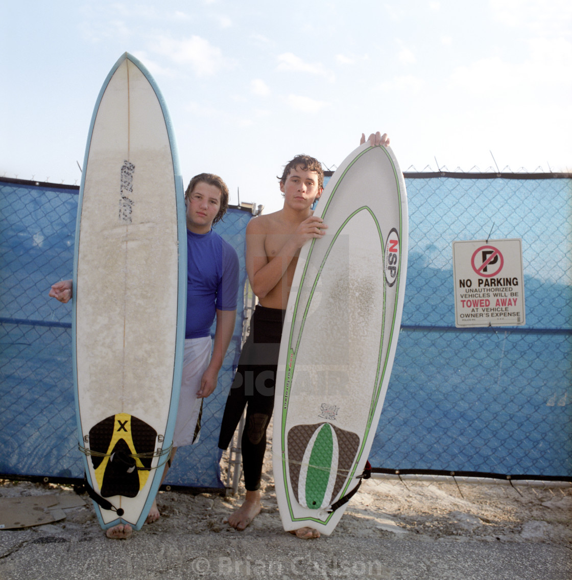 """Two adolescent boys holding surfboards near the beach"" stock image"