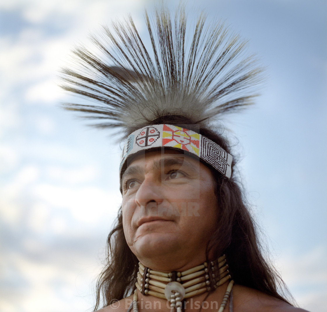 """Portrait of Native American male against blue sky with clouds"" stock image"