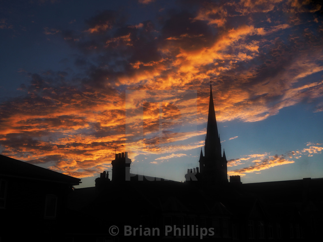 """Church Spire against dramatic sunset sky"" stock image"