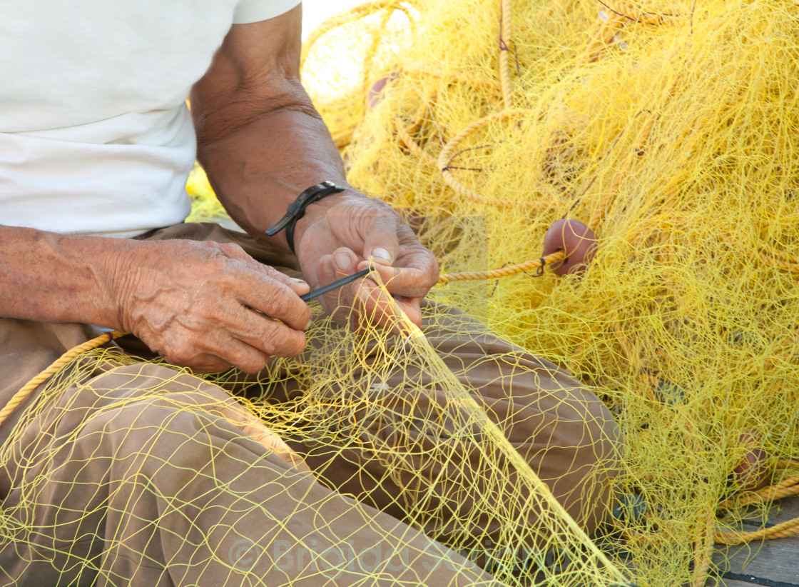 """Fisherman Mending His Fishing Net in Greece"" stock image"
