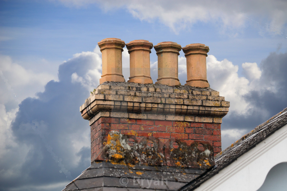 """Chimneys on an old roof in Ivybridge, Devon, England, a typical row of chimney pots in a row during the Victorian age when coal fires were popular"" stock image"