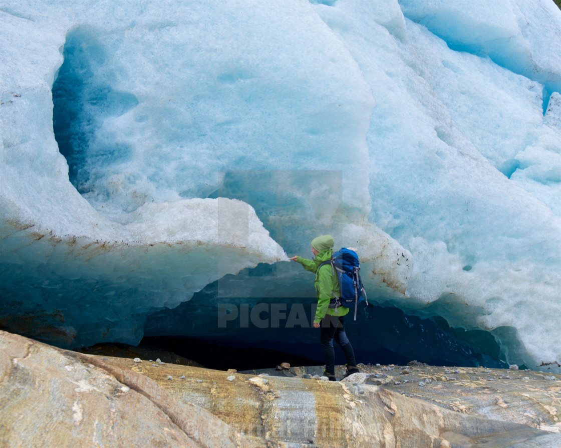 """Woman touching ice on a glacier"" stock image"