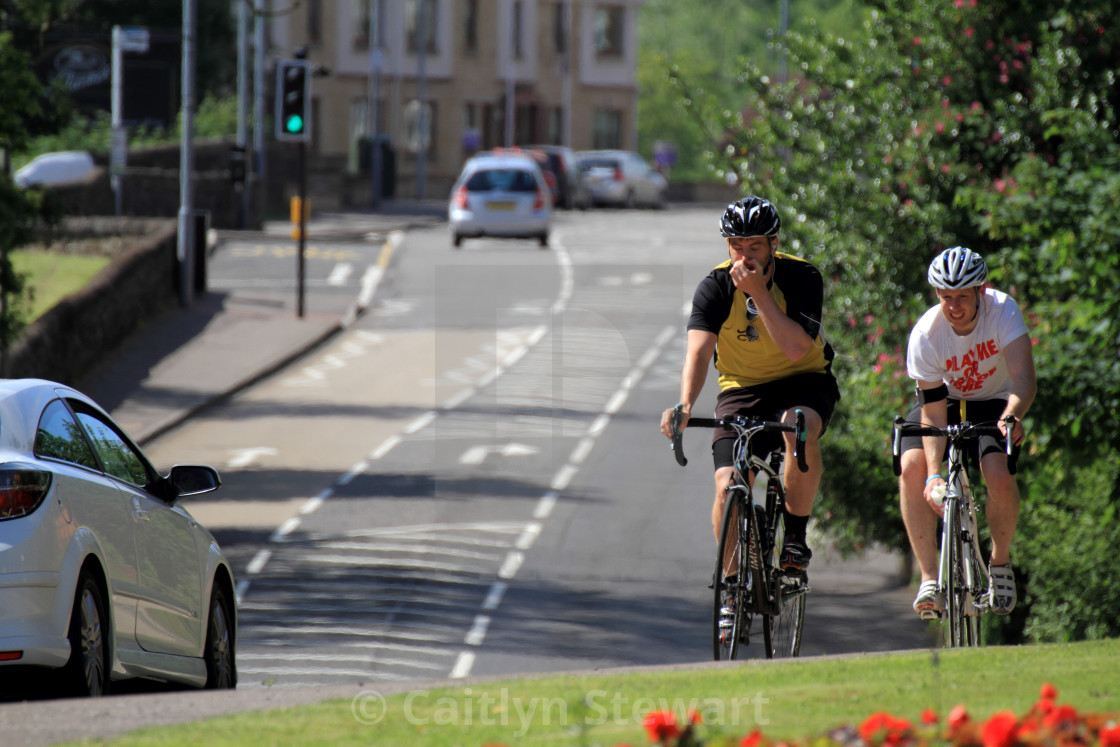 """""""Two male cyclists struggle in the heat, Lennoxtown, Glasgow, UK"""" stock image"""