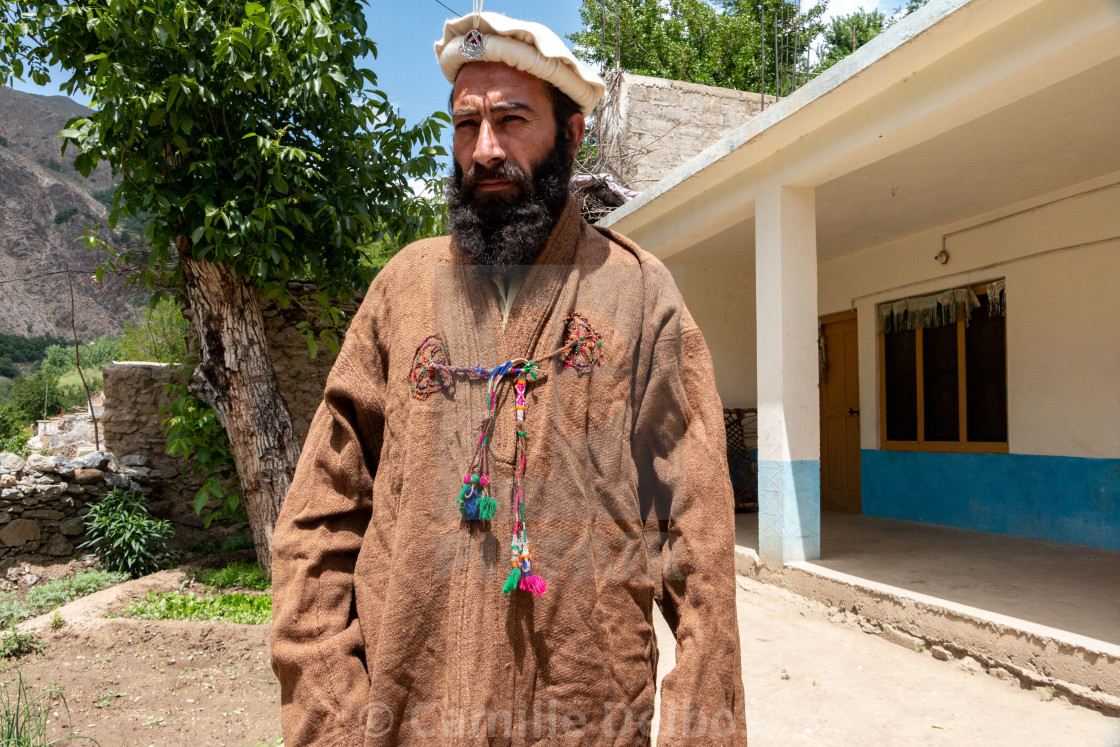 A man in afghan dress wear an old traditional wool jacket in