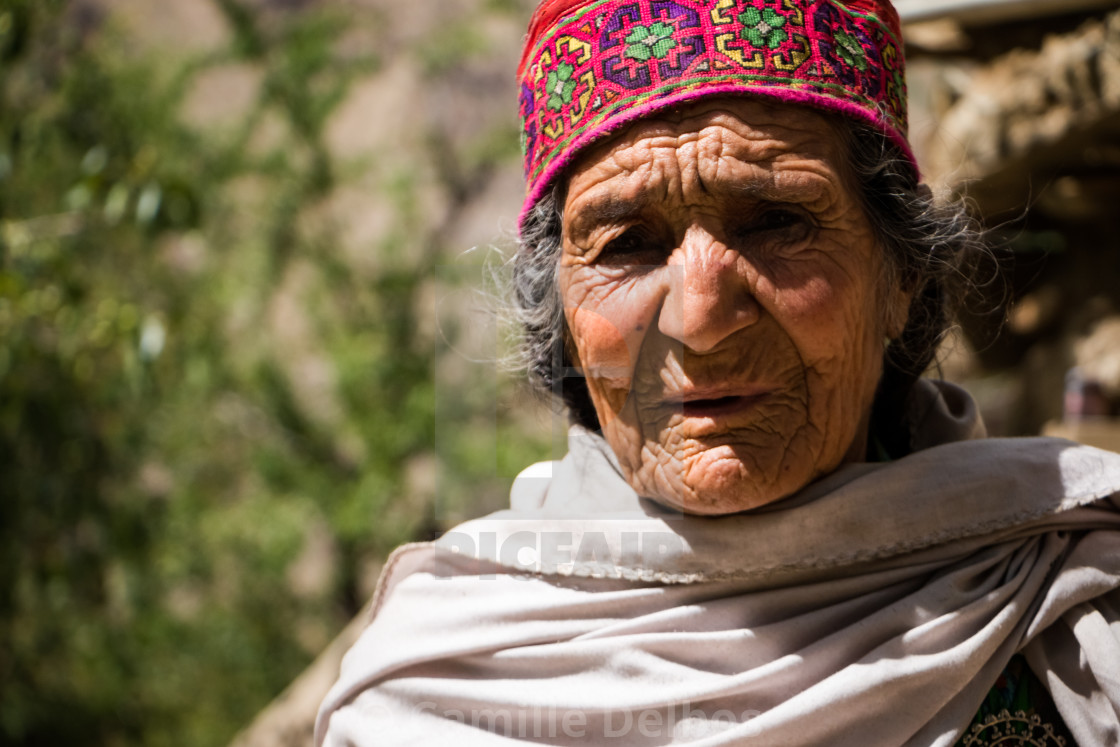Portrait of an old pakistani women with a traditional hat and a veil