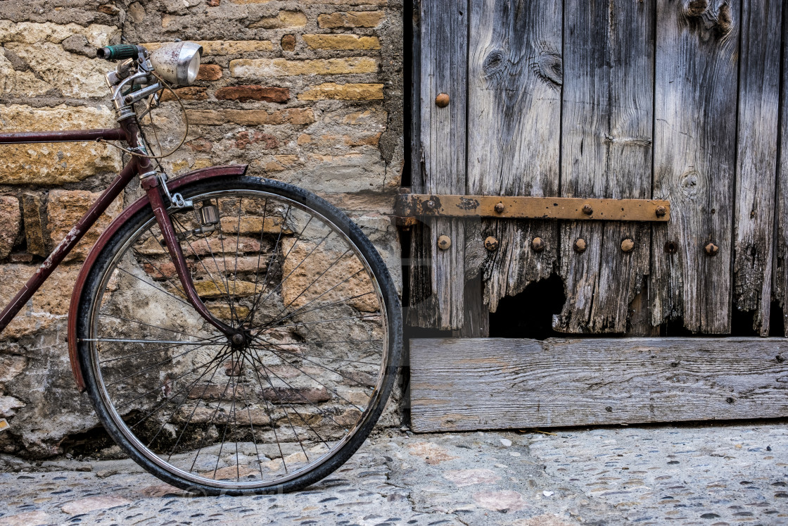 """Old bicycle recharged on a rustic wall in a village street of medieval origin in the village of Alquezar in the province of Huesca in Aragon Spain Europe"" stock image"