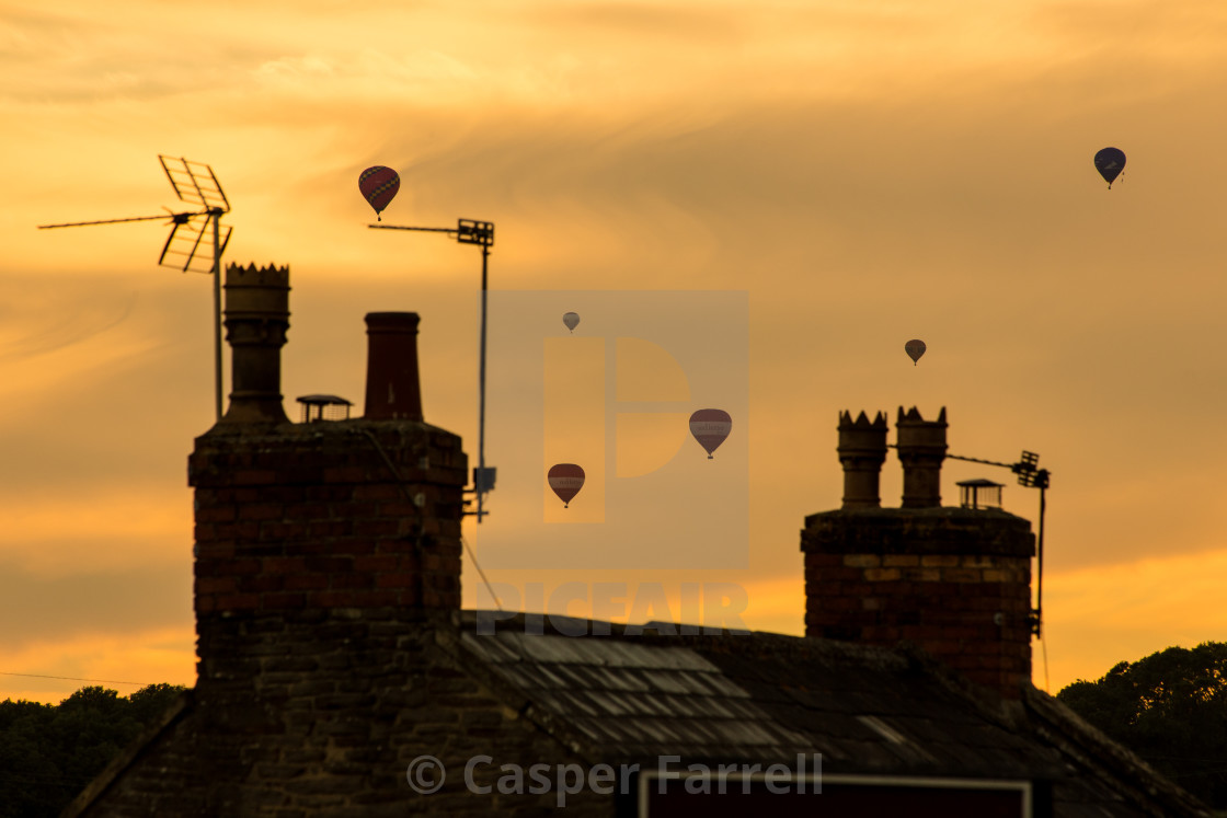 """Hot air balloons floating over roof tops and chimneys in golden sunset sky"" stock image"