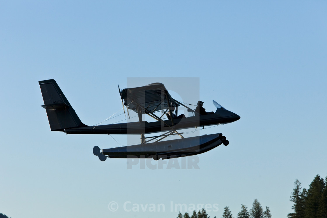 A float plane flying low above the water in Idaho  - License