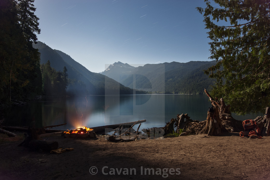 """""""Campfire by lake against sky"""" stock image"""