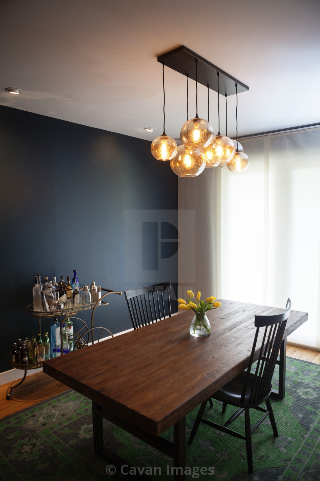 """Illuminated pendant lights over dining table at home"" stock image"