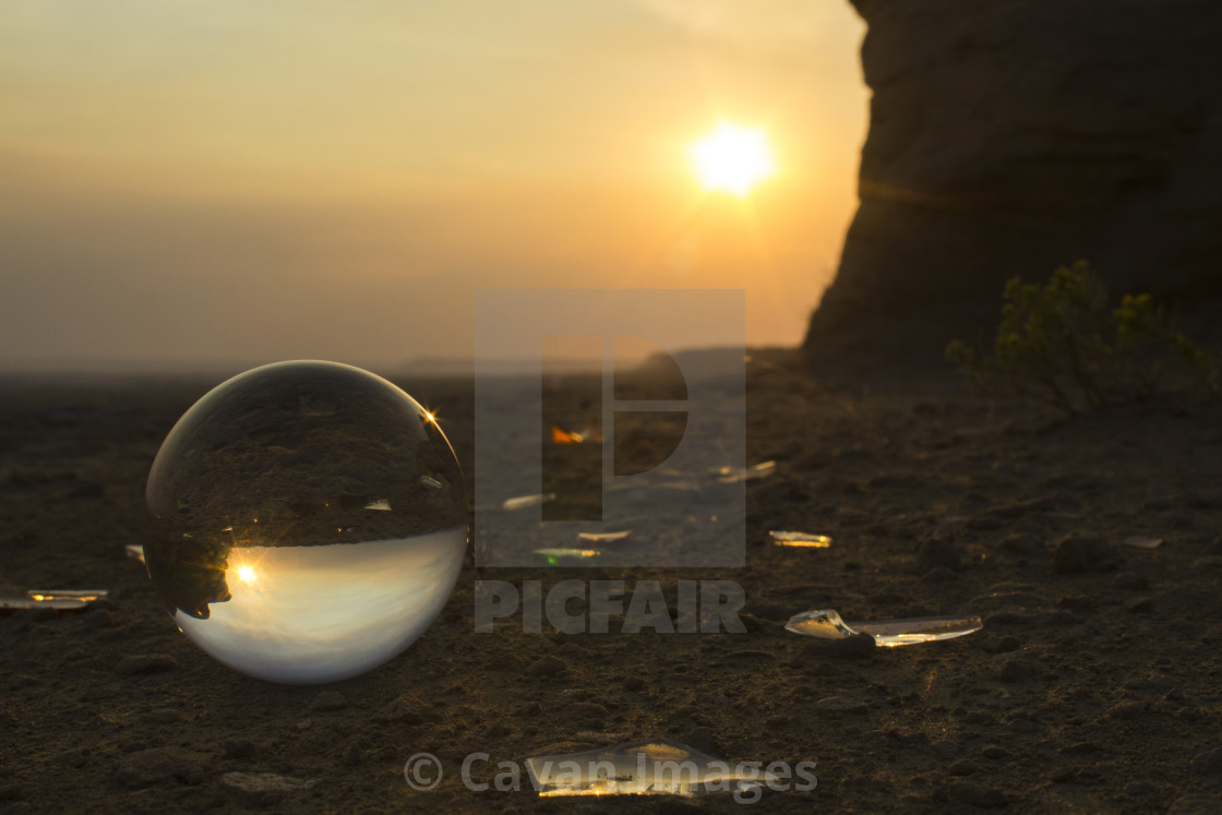 """Sun shining over sea shore reflection on crystal ball during sunset"" stock image"