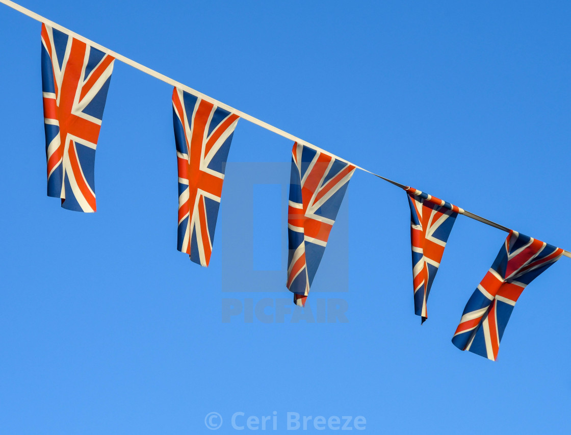 """Row of small Union Jack flags against a deep blue sky."" stock image"