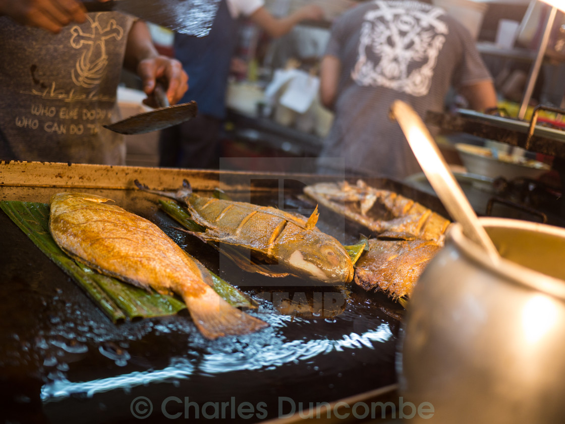 """Man Grills Fish in Asian Restaurant"" stock image"