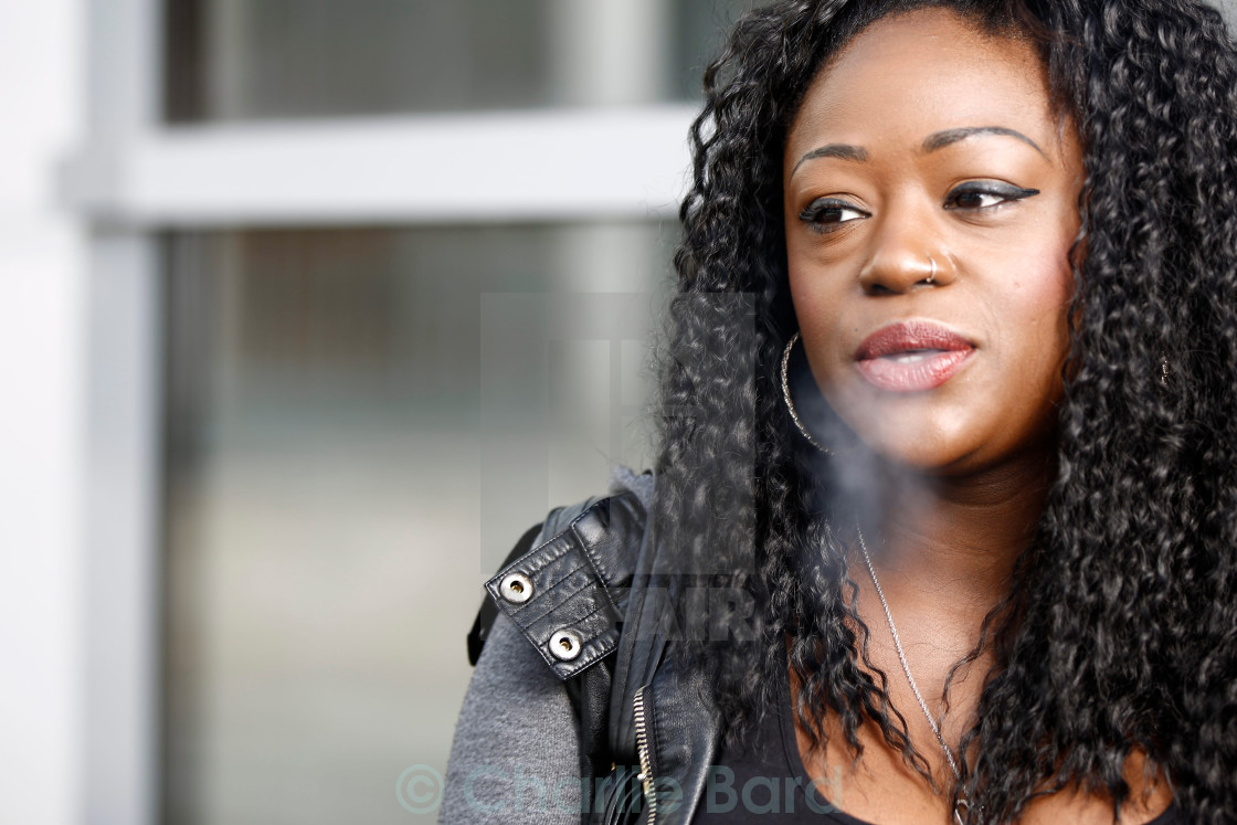 """Young African woman smoking a cigarette"" stock image"