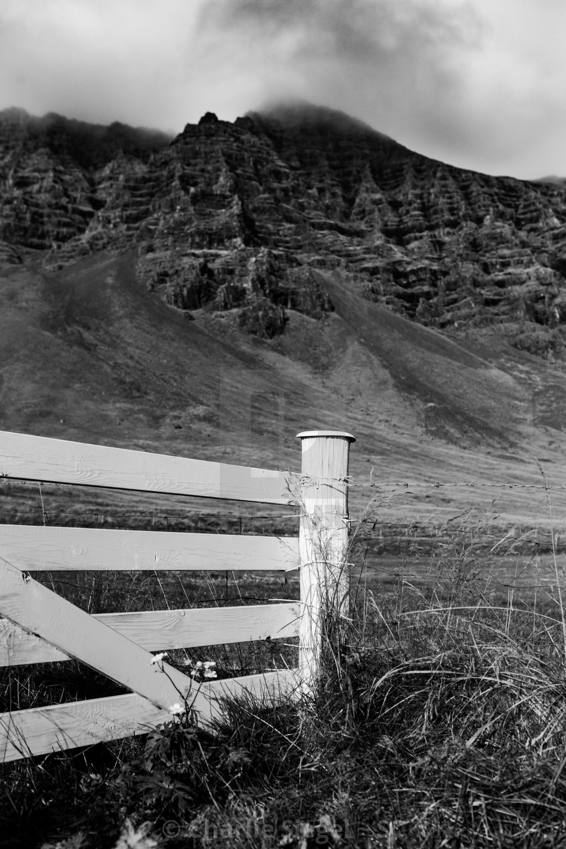 """White Picket Fence with Volcanic Hills Beyond in Iceland"" stock image"