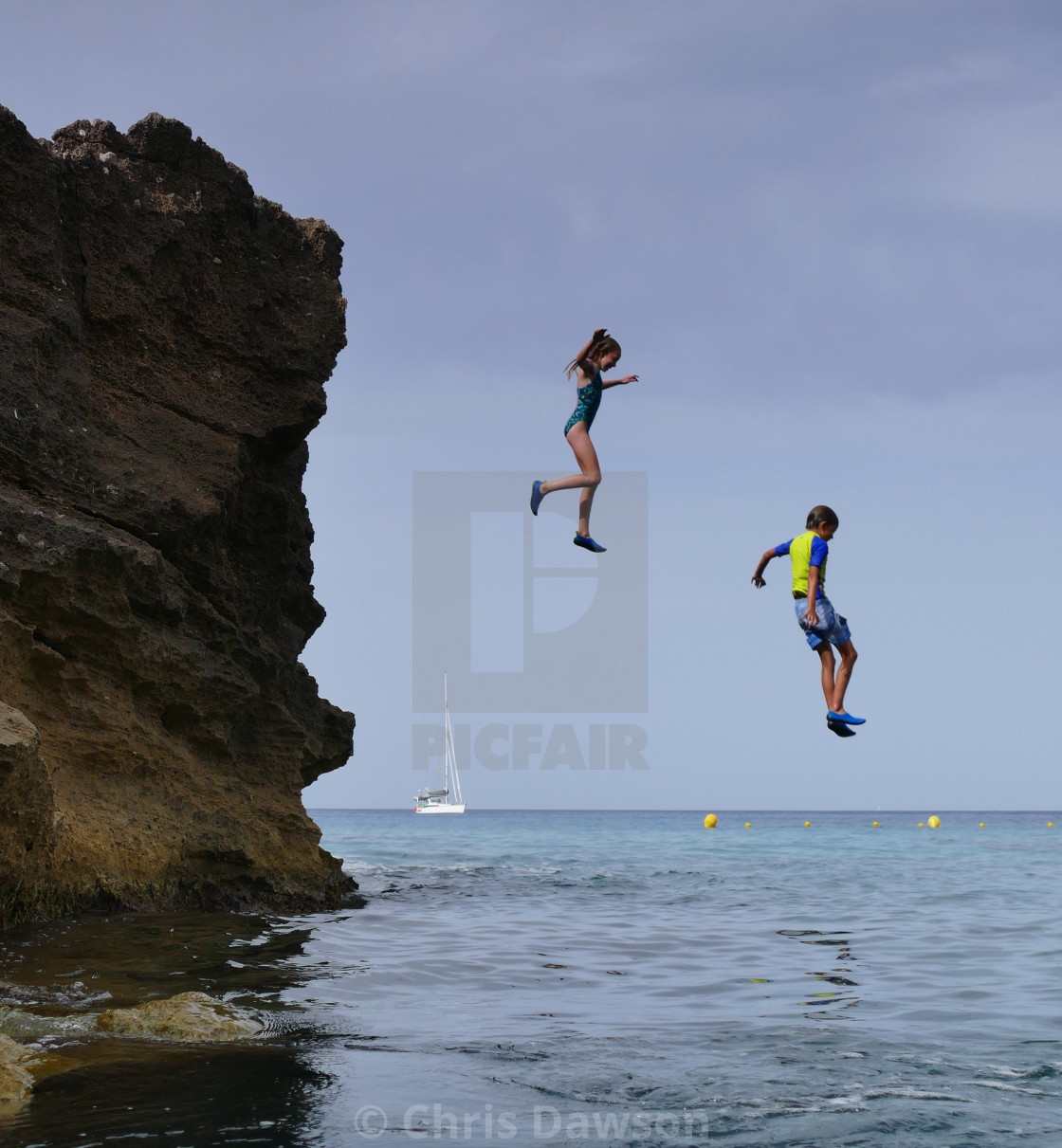 """Kids jumping off rocks in Mallorca"" stock image"