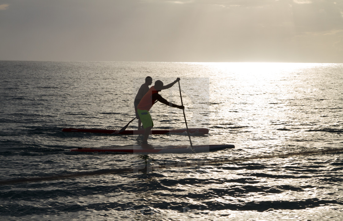 """""""Two Paddleboarders as the sun is setting"""" stock image"""