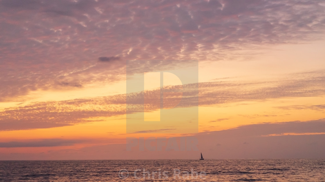 """Boat on the horizon at dawn off the Pacific coast of Mexico"" stock image"