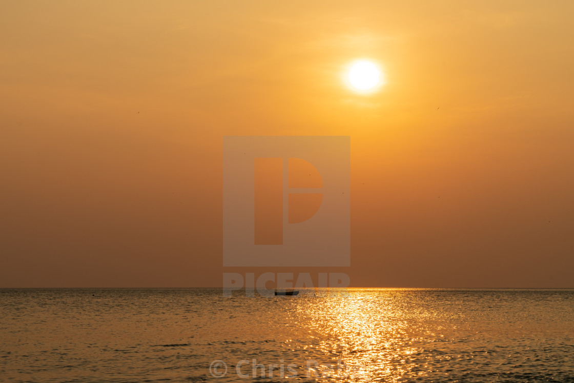 """Sunset in Costa Rica along pacific coast with single small boat on the ocean..."" stock image"