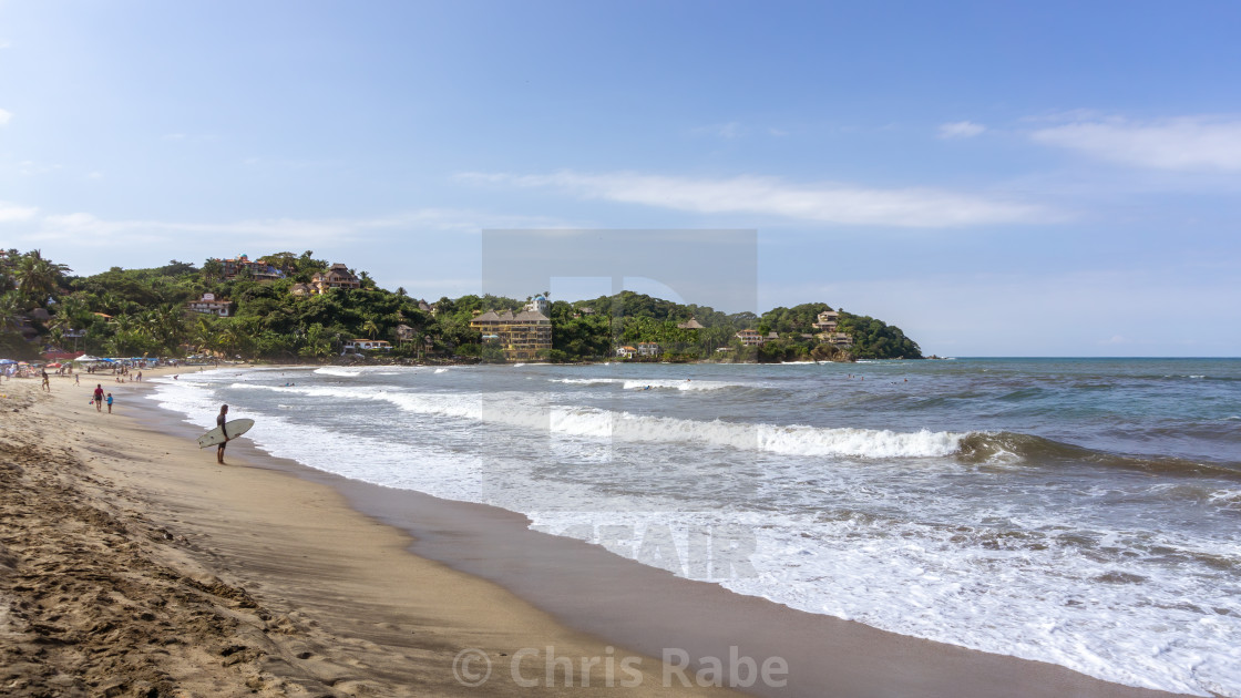 """Sayulita, Mexico - December 1 2015: A surfer stands watching the surf on the..."" stock image"