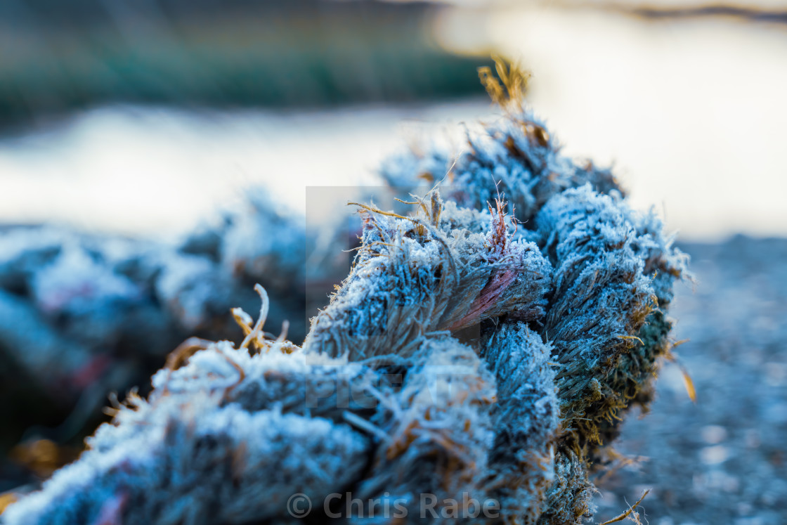 """Thick rope covered in ice from a heavy frost in winter, diiscarded next to..."" stock image"