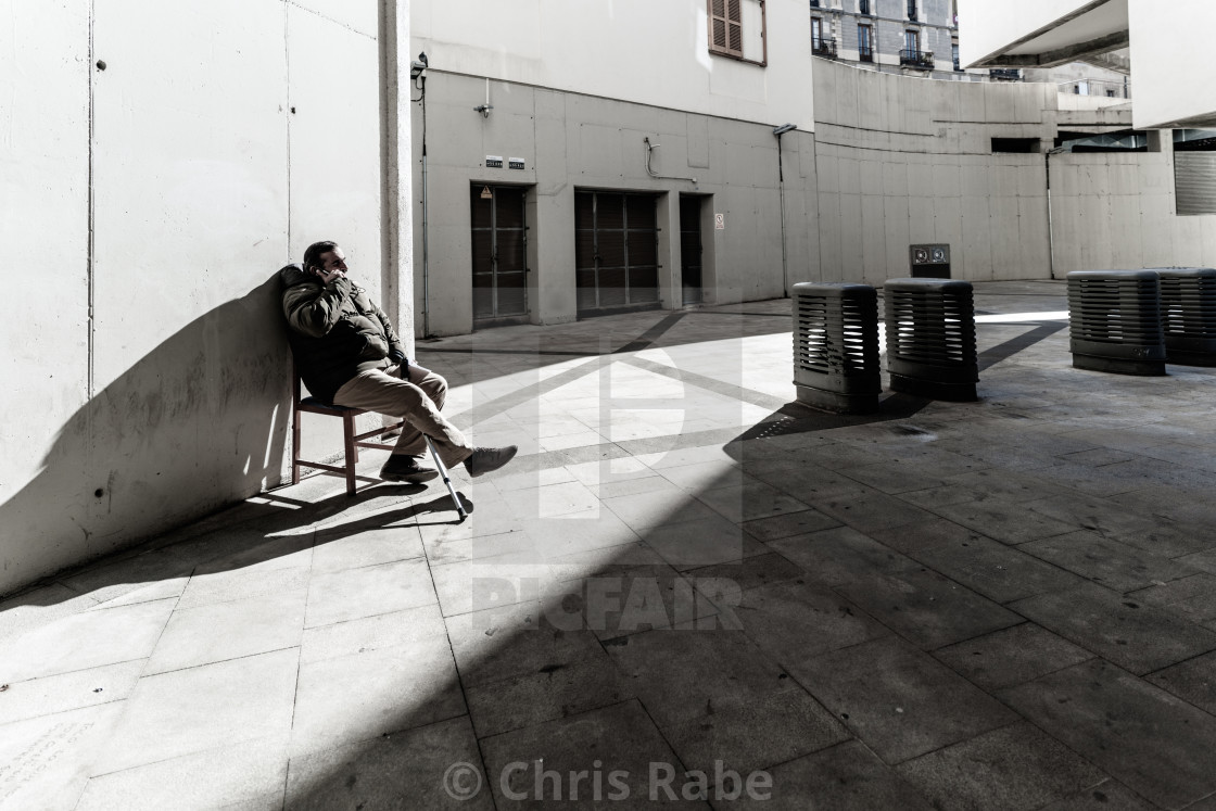 """Barcelona City, Spain - January 29 2018 : A man sits talking on his phone in..."" stock image"