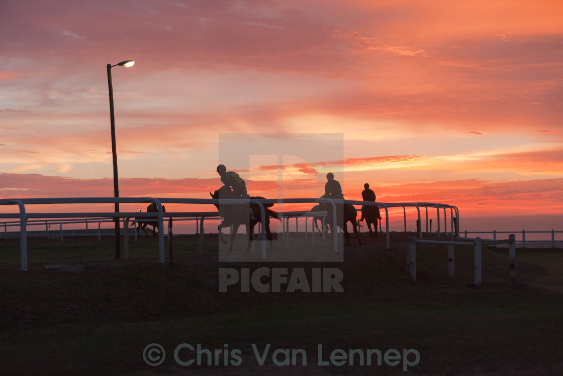 """Race Horses Riders Silhoutted Sunrise"" stock image"