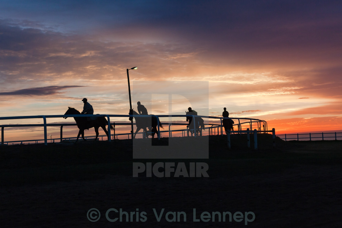 """Horses Riders Silhouetted Sunrise"" stock image"