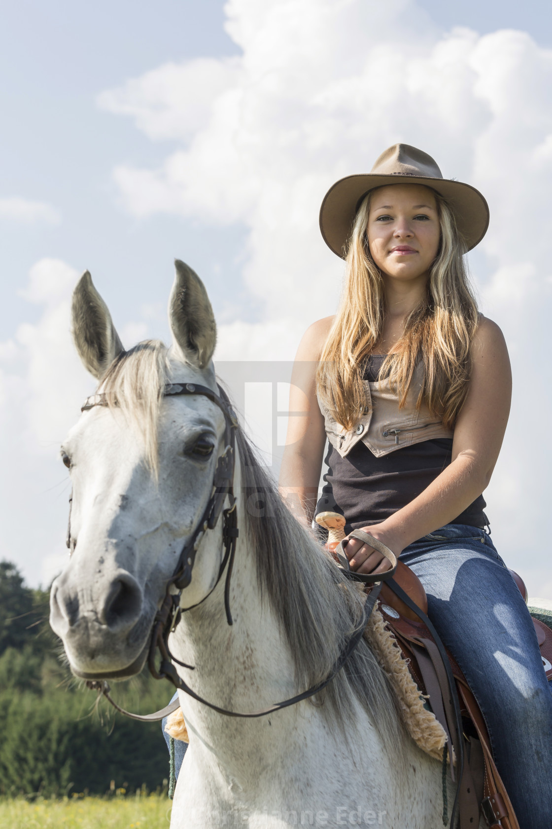 0ad60e53e Girl with cowboy hat sits on a horse - License, download or print ...