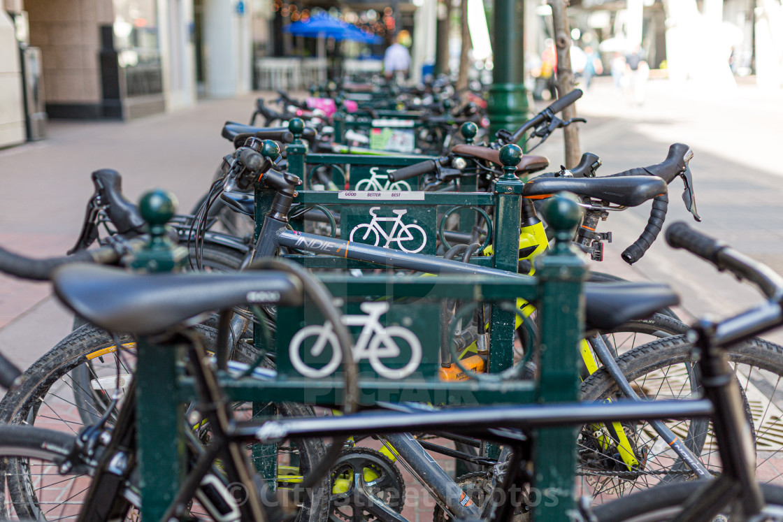 """A row of bike in a bike rack"" stock image"