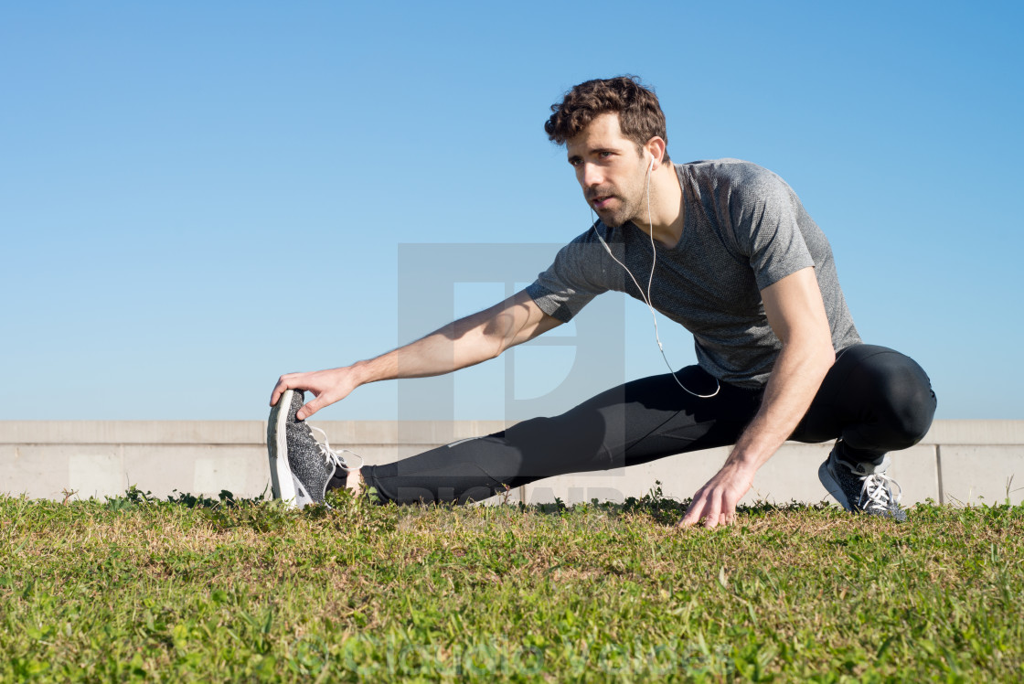 """""""man stretches leg in the ground"""" stock image"""