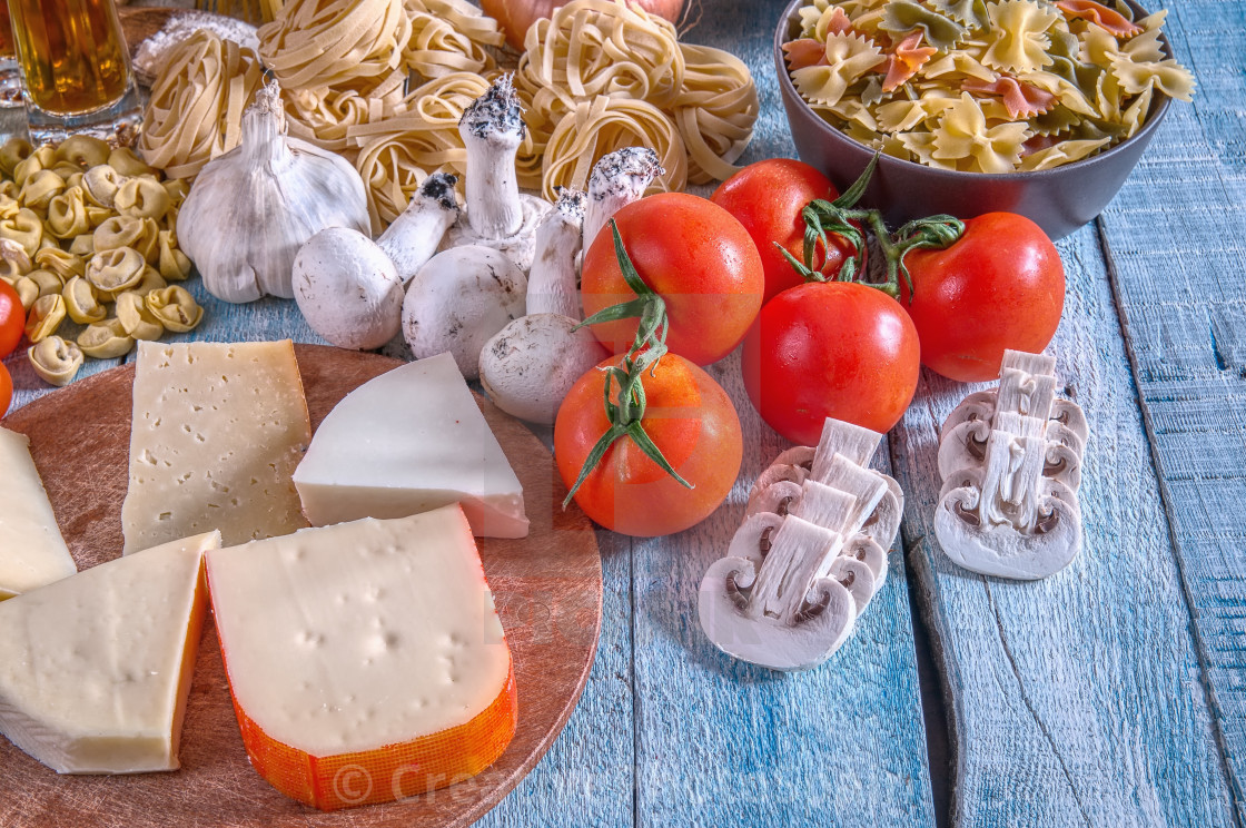 """Raw Pasta with ingredients on wooden background."" stock image"