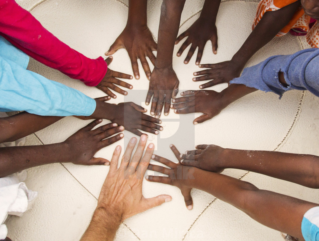 """Hands on sands of black children from Africa together with hand of a white man"" stock image"