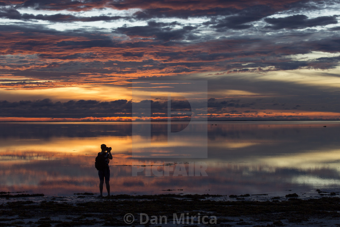"""Photographer taking pictures at sunset on beach with colorful and beautiful..."" stock image"