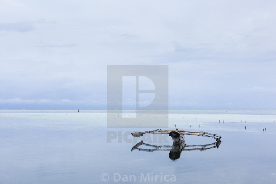 """Traditional fishing boat in Zanzibar with storm clouds at sunrise"" stock image"