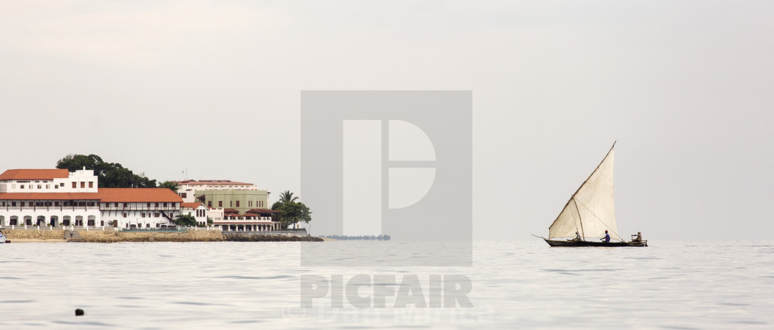 """""""Traditional fisherman boat in Zanzibar on ocean with rainy clouds."""" stock image"""