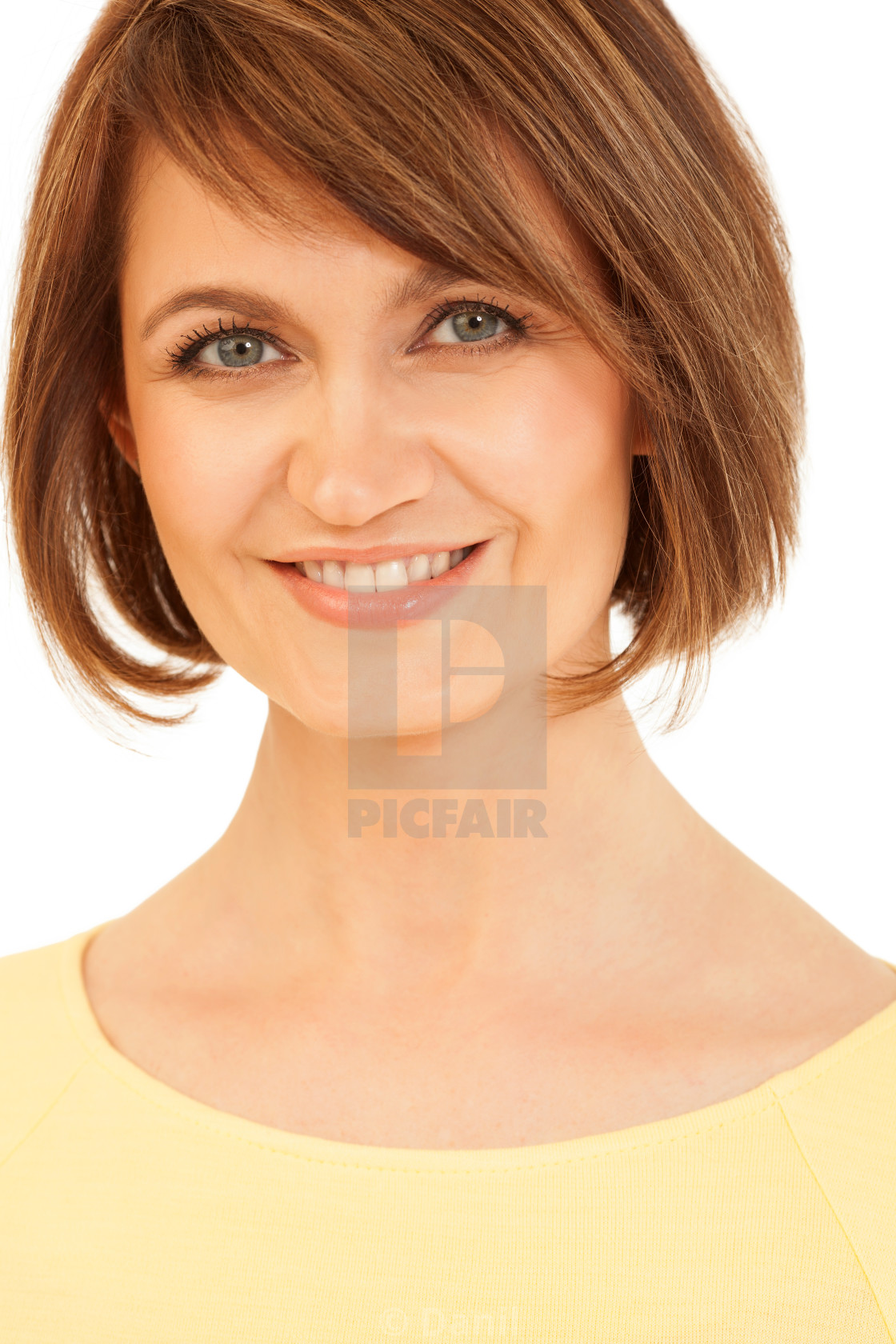 """Adult brunette in yellow smiling at camera"" stock image"