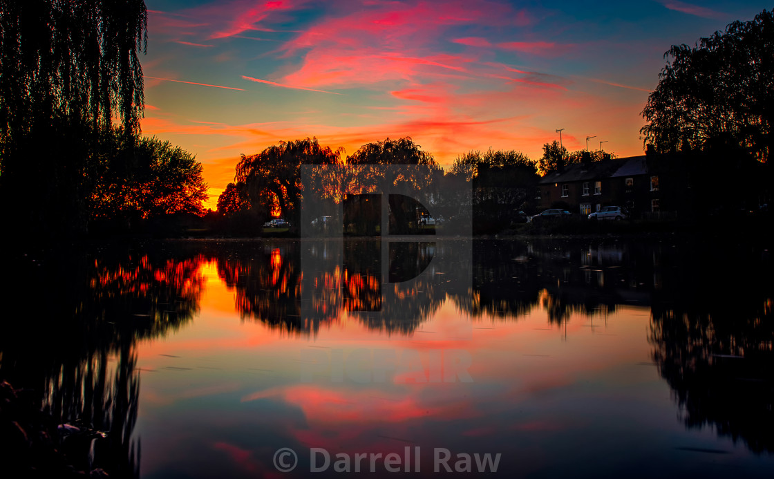 """Fiery sunset over a UK pond"" stock image"