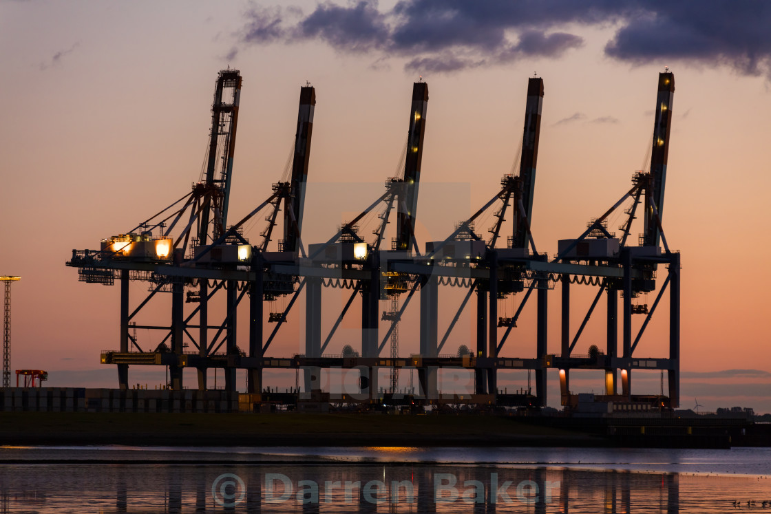 """Sunset or Sunrise Behind Cranes at Container Port"" stock image"