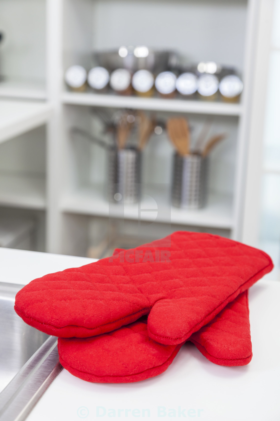 """Red Oven Gloves Mittens in a Modern Kitchen"" stock image"