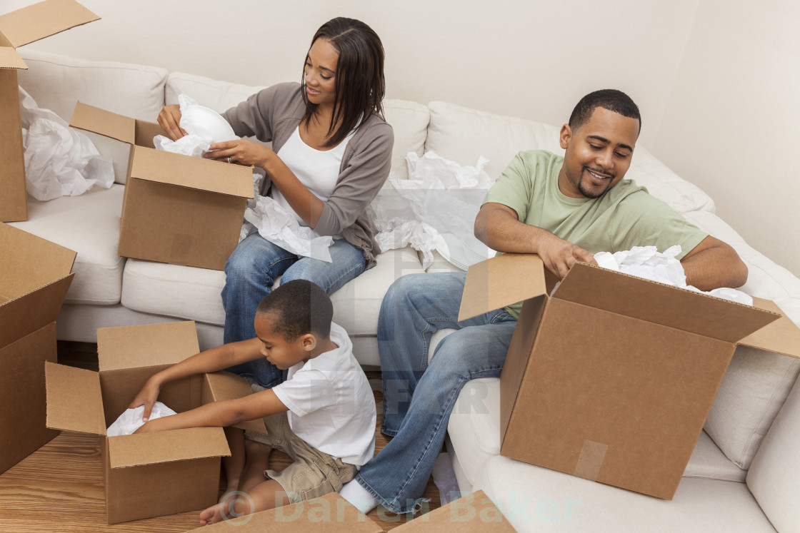 """African American Family Unpacking Boxes Moving House"" stock image"